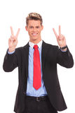 Business man showing two fingers or victory gesture. Happy smiling young business man showing two fingers or victory gesture, isolated over white background Royalty Free Stock Images