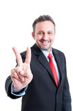 Business man showing victory sign or gesture. While smiling confident like a winner Royalty Free Stock Photography
