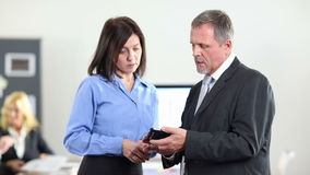 Business man showing woman smartphone in office stock footage