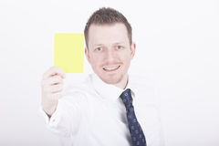 Businessman showing yellow card Royalty Free Stock Image