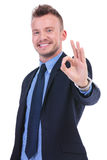 Business man shows ok gesture. Young business man showing the ok gesture with a smile on his face. on white background Stock Images