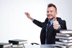 Business man shows ok while writing Royalty Free Stock Photo
