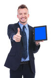 Business man shows tablet and thumb up. Young business man showing a tablet and the thumb up gesture while smiling at the camera. on white background Stock Photos