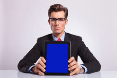 Business man shows tablet. Young business man sitting at the desk and showing you his tablet, on gray bacckground Royalty Free Stock Image
