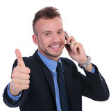 Business man shows thumb up while on phone Stock Photos