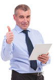 Business man shows thumb up with tablet in hand Royalty Free Stock Images