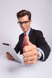 Business man shows thumb up. Young business man at the desk, holding a tablet and showing thumbs up and looking at the camera Royalty Free Stock Photo