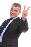 Business man shows victory gesture Royalty Free Stock Photos
