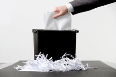 Business man shredding a document. Hand of businessman putting a document in paper shredder  with pile of previously shredded paper Royalty Free Stock Photography
