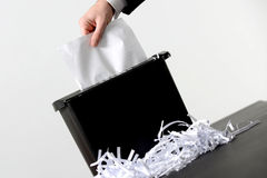 Business man shredding a document. Hand of businessman putting a document in paper shredder  with pile of previously shredded paper Stock Photo