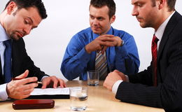 Business man signing a contract. Three businessmen sitting at a table negotiating and signing a contract royalty free stock images