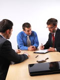 Business man signing a contract. Three businessmen sitting at a table negotiating and signing a contract royalty free stock photography