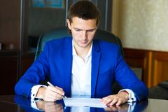 Business man signing a contract in big office Stock Images