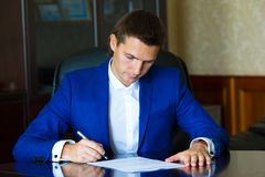 Business man signing a contract in big office Stock Photo