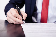 Business man signing a contract. A hand holding a fountain pen and about to sign a letter. Styling and small amount of Stock Photography
