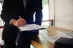 Business man signing contract making a deal with real estate age stock photo