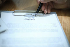 Business man signing a contract. In modern light office Stock Image