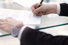 Business man signing a contract. In modern light office Royalty Free Stock Photos
