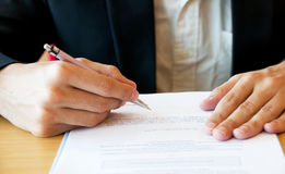 Business Man Signing Documents. A business man signing a document on a table Royalty Free Stock Photos