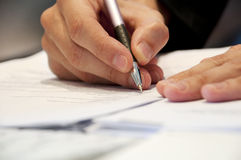 Business Man Signing Documents. Business man working on paper work Royalty Free Stock Images