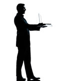 Business man silhouette holding offering com Royalty Free Stock Photography