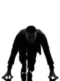 Business man silhouette on starting block stock photography