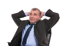 Business man sits on chair with hands behind head Stock Photography
