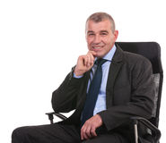 Business man sits on chair and looks at you Stock Images