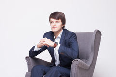 Business man sits on chair over white background Royalty Free Stock Photo