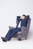 Business man sits on chair over white background Stock Photos