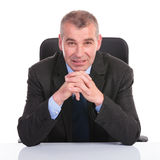 Business man sits with hands together Stock Photography