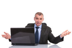 Business man sits at laptop and welcomes you Stock Images