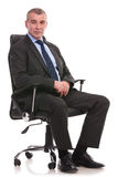 Business man sits on an office chair Royalty Free Stock Photography