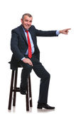Business man sits and points away Stock Images