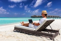 Business man sits on a tropical beach with his laptop and works. Business man on vacation sits on a sunbed at the tropical beach with his laptop and works royalty free stock photography