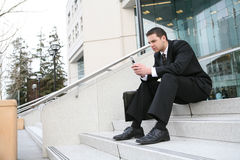 Business Man Sitting. A handsome business man sitting on stairs outside company Stock Photography