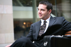 Business Man Sitting. A handsome business man sitting on a bench Royalty Free Stock Photo