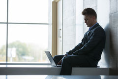 Business man sitting alone on a bench with laptop Royalty Free Stock Photos
