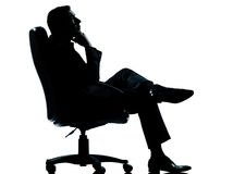 Business man sitting armchair relaxing silhouette. One caucasian business man relaxing thinking sitting in armchair silhouette Full length in studio isolated on Royalty Free Stock Image