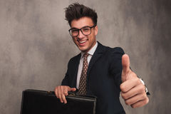 Business man sitting with  briefcase and makes the ok sign Stock Photos