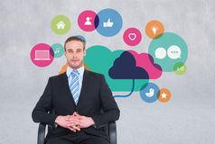 Business man sitting in chair with icons on the wall Stock Images