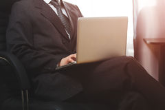 Business man sitting in chair and working on computer in his office while sunset shine to the window. Native colors Royalty Free Stock Image