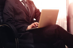 Business man sitting in chair and working on computer in his office while sunset shine to the window. Warm toning. Stock Photography