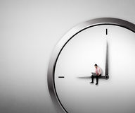 Business Man Sitting On The Clock Royalty Free Stock Image