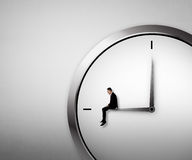 Business man sitting on the clock Stock Image
