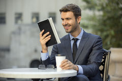 Business man sitting at coffee shop reading a tablet device Royalty Free Stock Photography