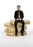 Business man sitting on coins Royalty Free Stock Images