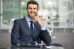 Business man sitting confident with smile portrait. A handsome young business man in a suit sits at a coffee shop smiling proud and confident for a portrait Stock Images
