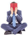Business man sitting cross legged covering his face with a book Stock Photo