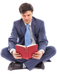 Business man sitting cross-legged and reading Royalty Free Stock Photo